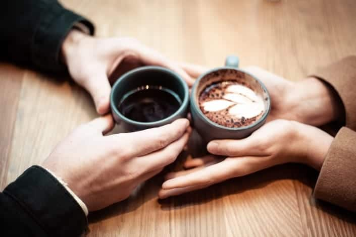 Couple holding hands with each other and their coffee cups