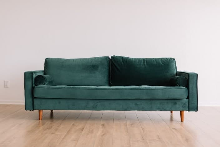 Green velvet couch in center of wooden floors