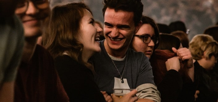 Guy intently smiling at girl amidst crowd