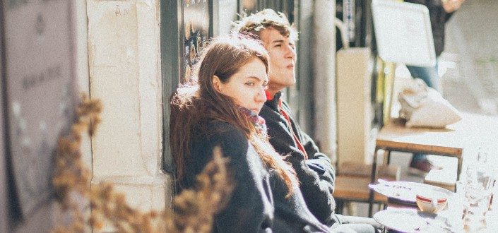 Couple leaning against a wall observing people