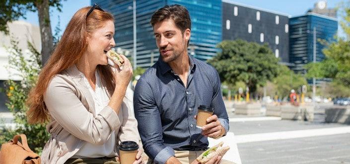 Couple eating outside near building