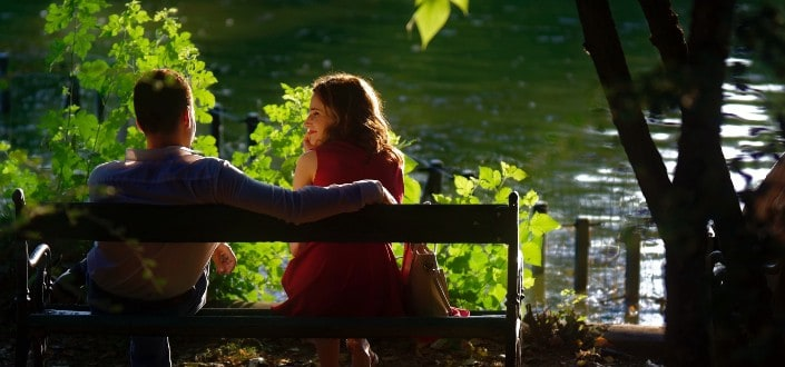 couple sitting on a bench by the river