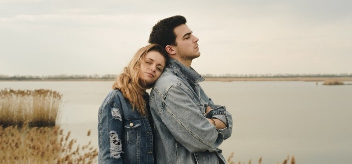 Girl leaning her head on guy's shoulder from behind