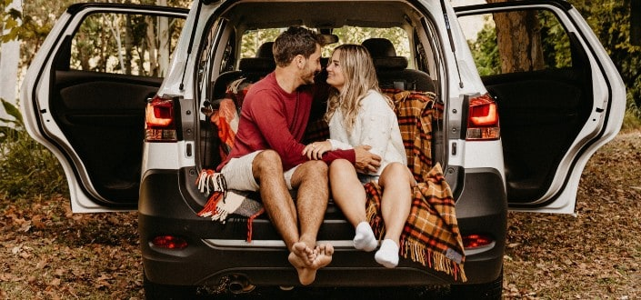 Couple having a cozy afternoon at trunk of car