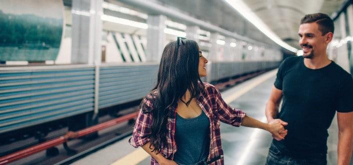 Girl holding guy's hand on train station