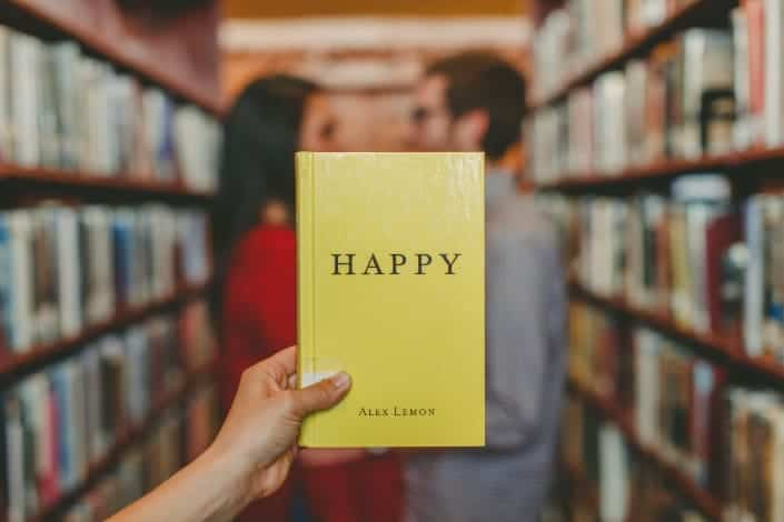 Couple in the background with book entitled Happy in front