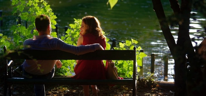 Couple sitting on a bench in front of a lake
