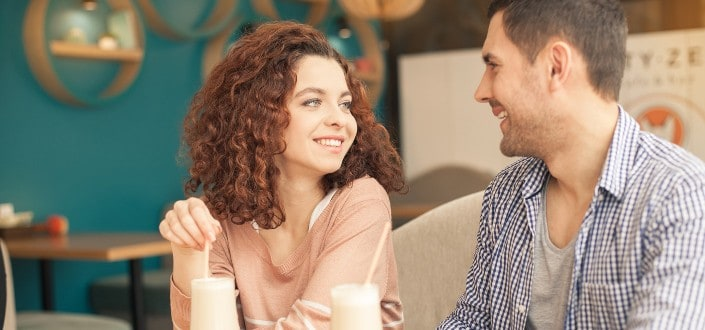 Girl and guy smiling at each other at a cafe