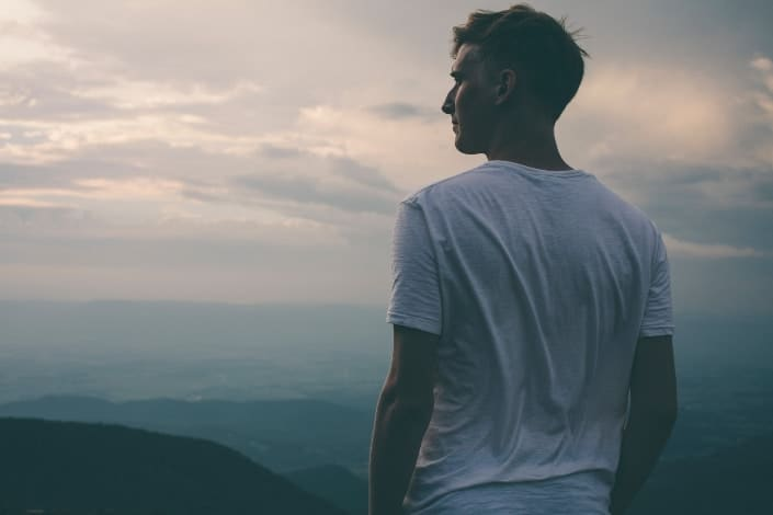 Guy in white shirt staring in the distance over a hill