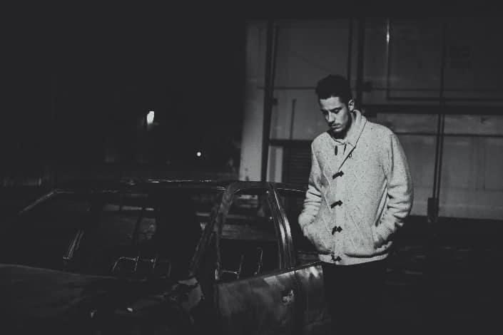 Guy in solemn mood standing beside a car