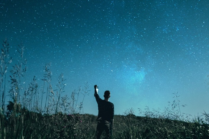 Guy holding his hand up in the starry sky