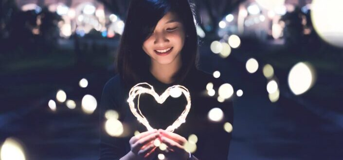 smiling woman holding a heart-shaped light at night