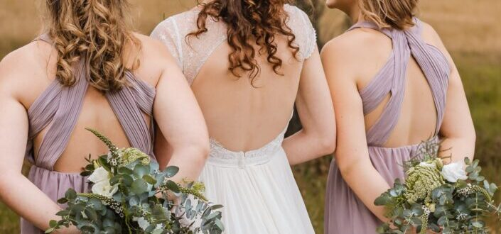 Back of two bridesmaids and bride