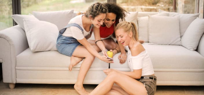 Happy divHow to Meet men - Ask a friend to set you up.jpgerse friends laughing with smartphone at home