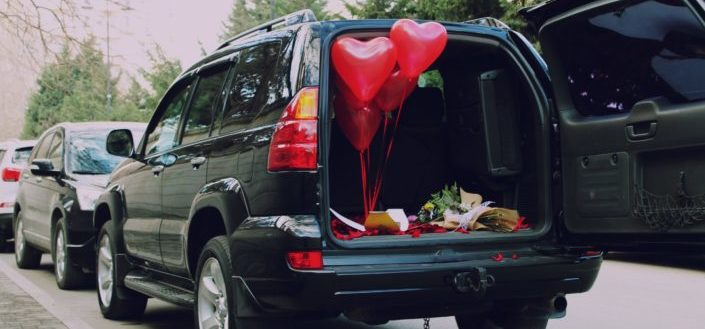 Open car trunk with three heart-shaped balloons and flowers