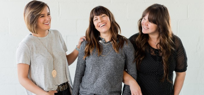 three women smiling with a white wall background