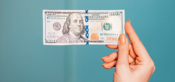 one hundred dollar bill held by a woman's hand