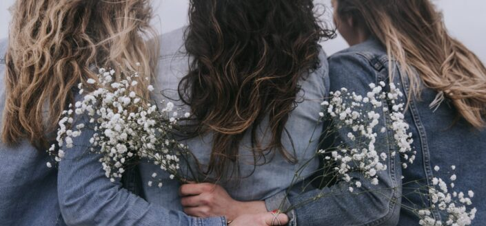 three women's backs with their hands holding dainty white flowers