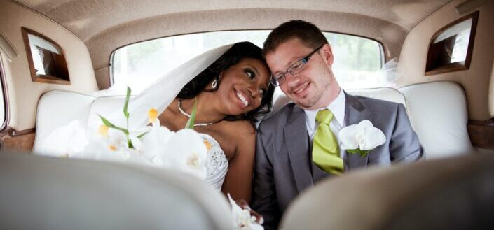 bride and groom sitting closely in the backseat of a car