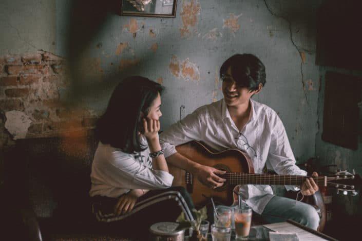 Man playing guitar while taring at the girl.