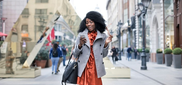 Woman Walking while Texting and Holding Her Sunglasses