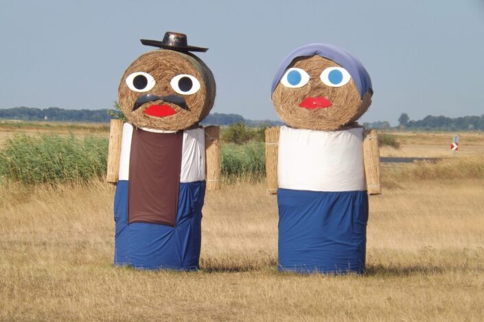 Dressed male and female human haystacks.