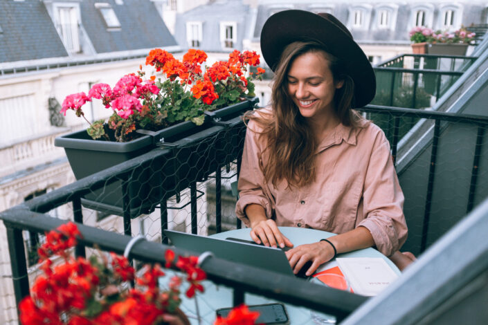 Lady, smiling while doing something on her laptop.