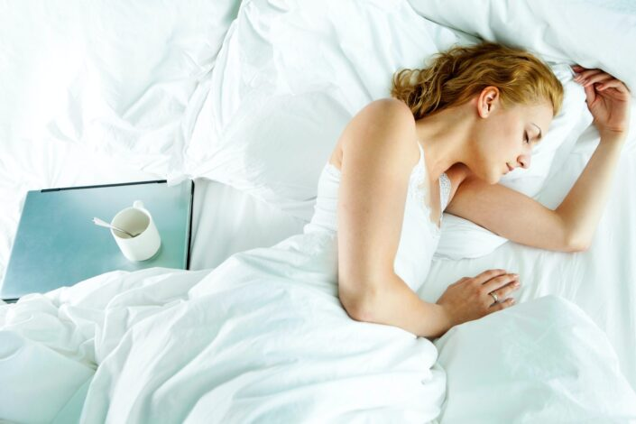 Woman, sleeping beside her laptop and empty cup.