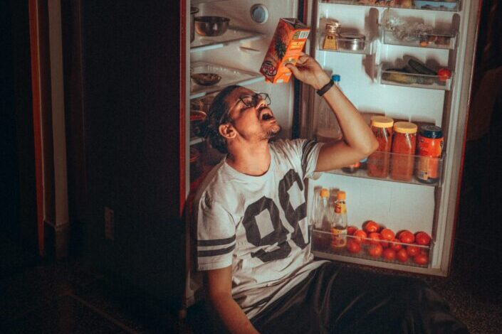 Man, emptying the juice box beside the fridge.