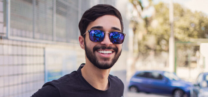Guy with sunglasses sweetly smiling.