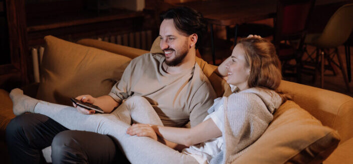 Couple, cuddling on a couch, happily watching TV.