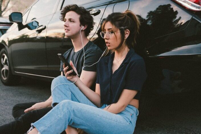 Couple, sitting against a car, listening to music together.