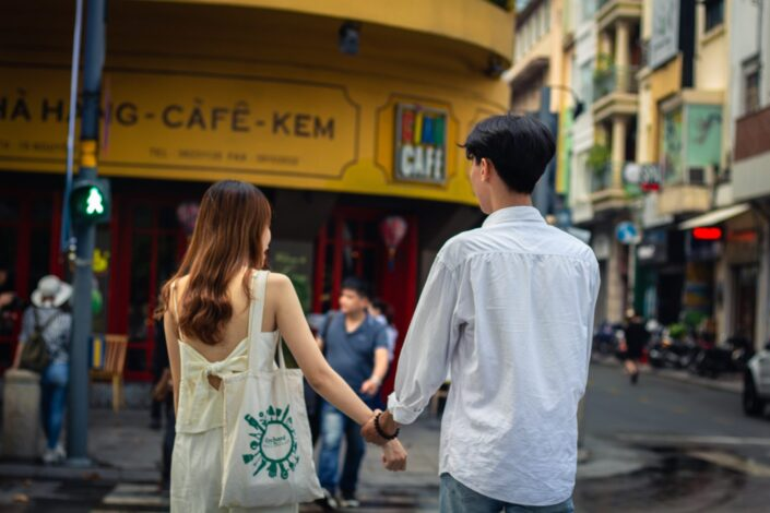 Couple, holding hands while crossing the street.