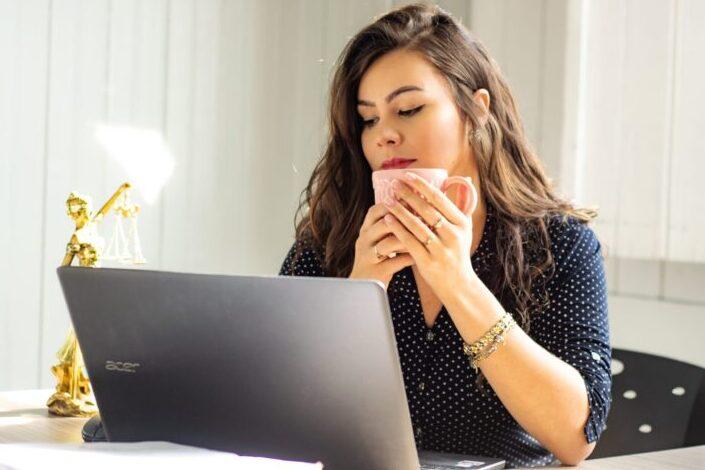 Girl, having coffee, watching something on her latop.