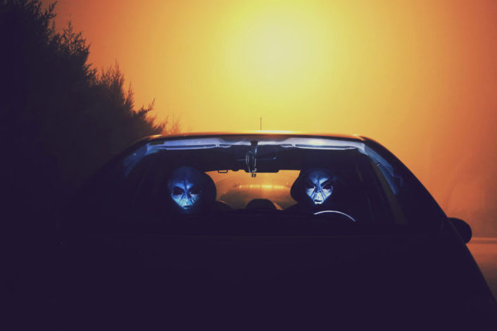 Two alien-faced creatures, riding a car.