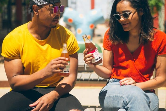 Couple drinking coolers together on a sunny day.