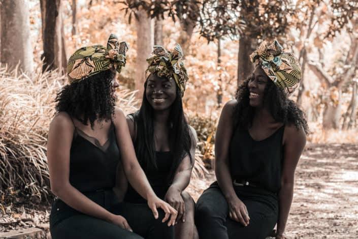 Three girls in headdresses having fun chatting outside.