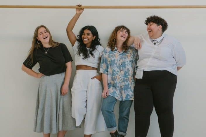 Girls standing against a wall, laughing.