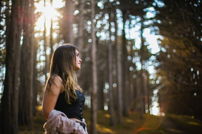 Girl, standing in the middle of the woods.