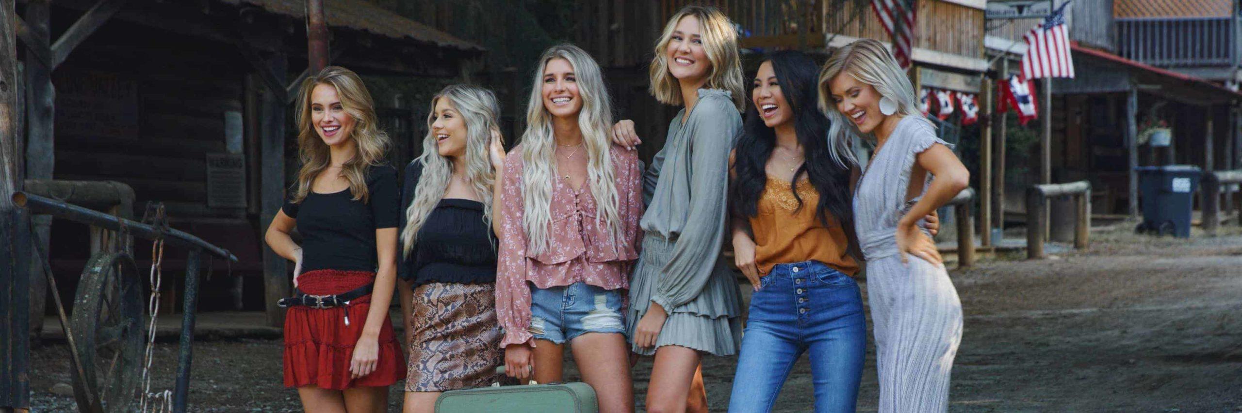 Six girls joyfully pose beside each other.