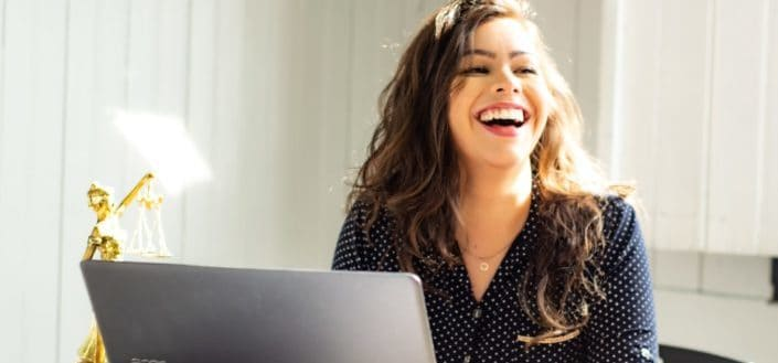 Delighted woman in front of her laptop.