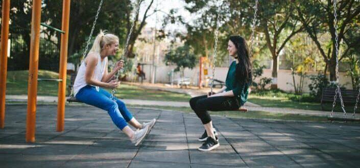 Two girls having fun talking while swinging.