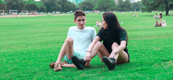young couple resting on lawn in park