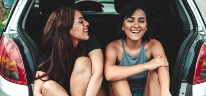 Bestfriends chatting at the back of a car.