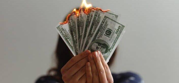 Burning fake dollar bills.