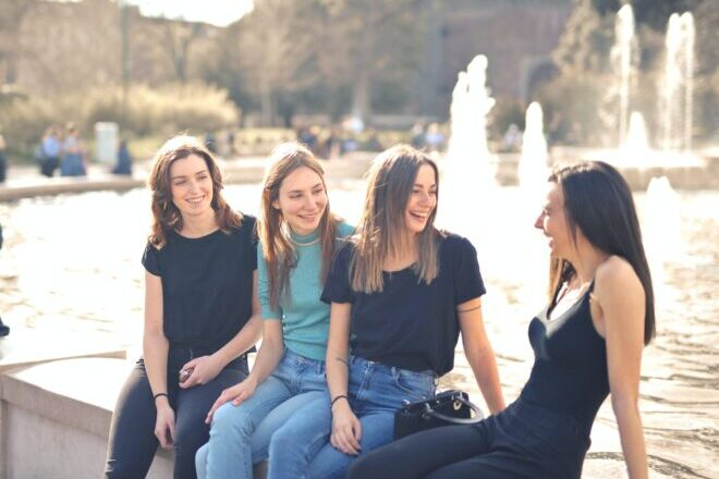 Girl friends sharing laughter beside a fountain. - deep questions to ask