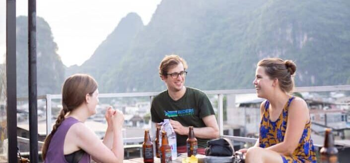 Friends, chatting over bottles of beer, overlooking a magnificient view.