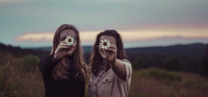 Two girls holding out a flower each.