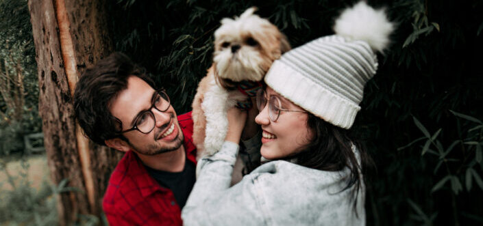 Couple playing with their pet dog outside