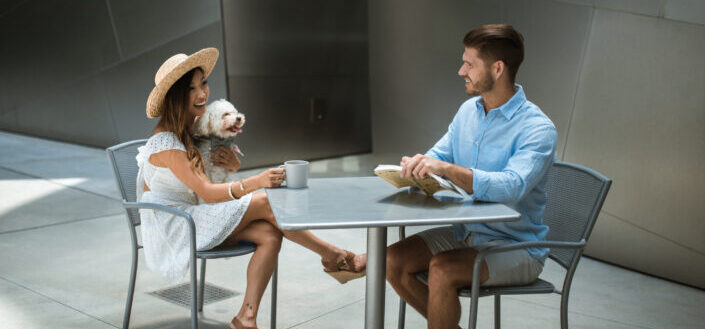 happy couple seating with a dog